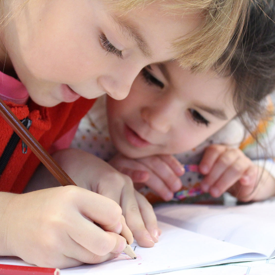 Children writing something on a notebook