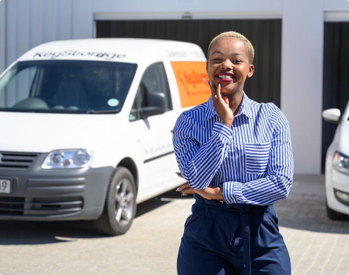A woman posing happily in front of parked vehicles