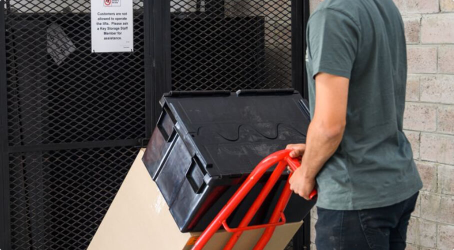 Man carrying box containers using a trolley