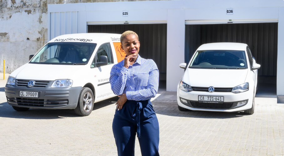 A woman posing in front of parked vehicles